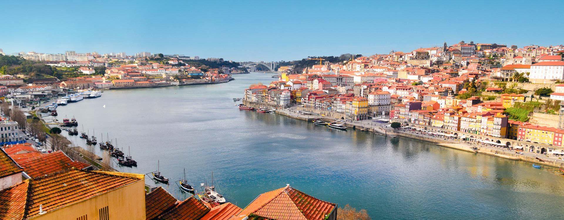 E-Velo Reisen entlang des Jakobweges - Blick über den Douro in Porto mit den Portweinschiffen (barcos rabelos) im Vordergrund