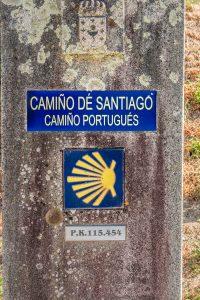 E-Velo Reisen entlang des Jakobweges - solche Jakobsmuschel-Wegweiser stehen auf der spanischen Seite und zeigen die Entfernung nach Santiago de Compostela an